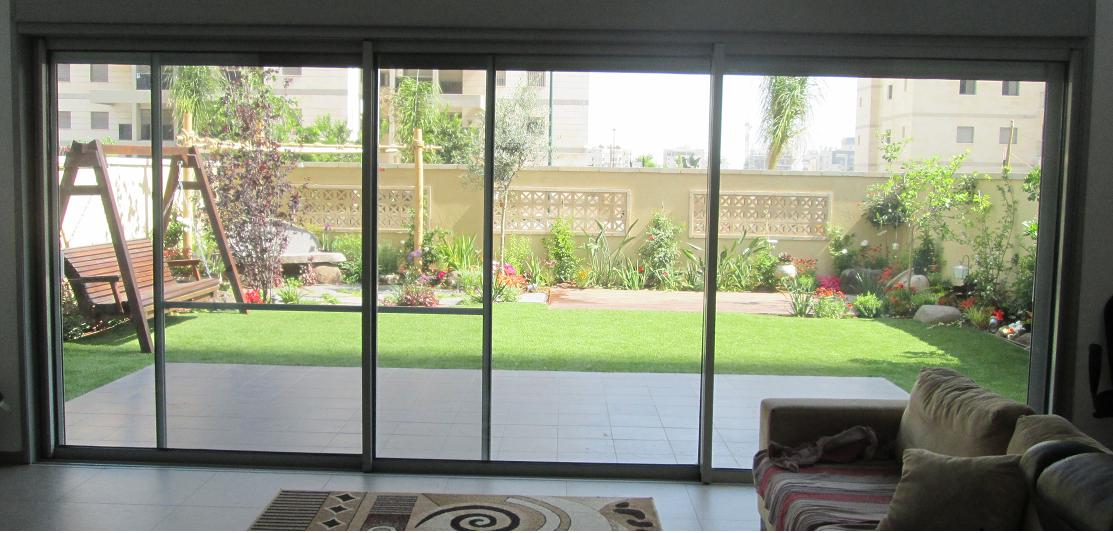 מבט אל הגינה מחלון הסלון
