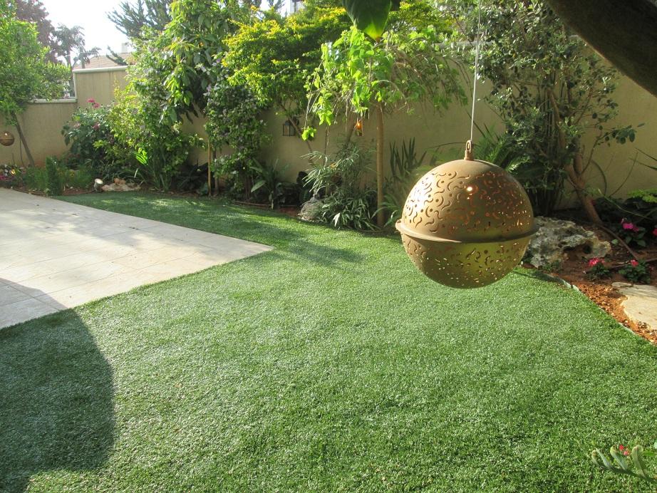 דשא עוטף את פינת הריצוף וצמחיה מעוצבת