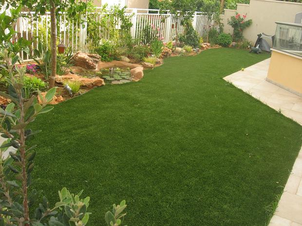 גינה מעוצבת עם דשא שמגיע עד לבריכת הנוי ועיצוב הצמחיה