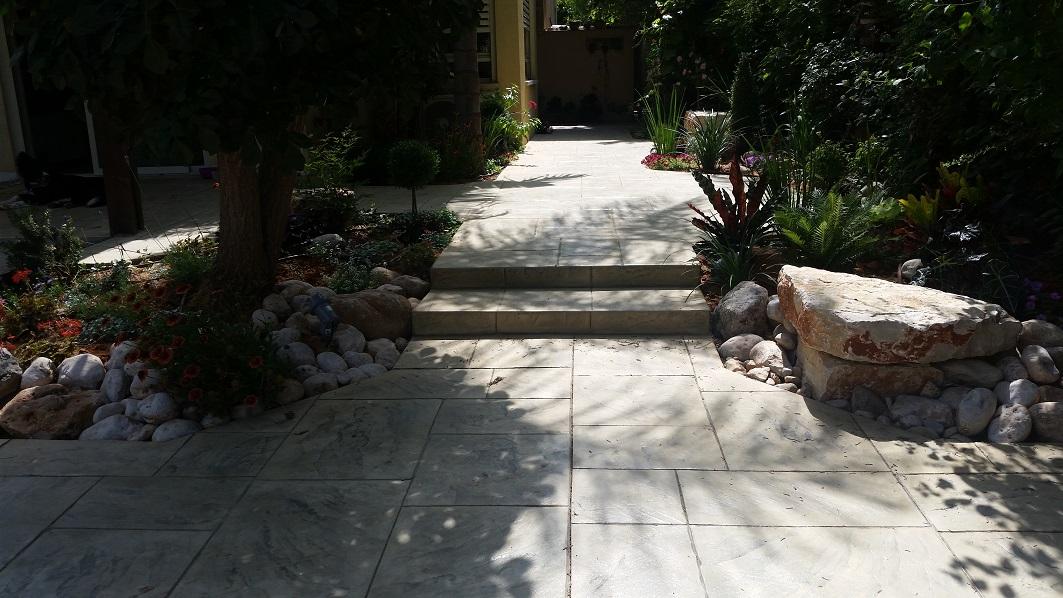 מימין ספסל סלע בכניסה לגינה