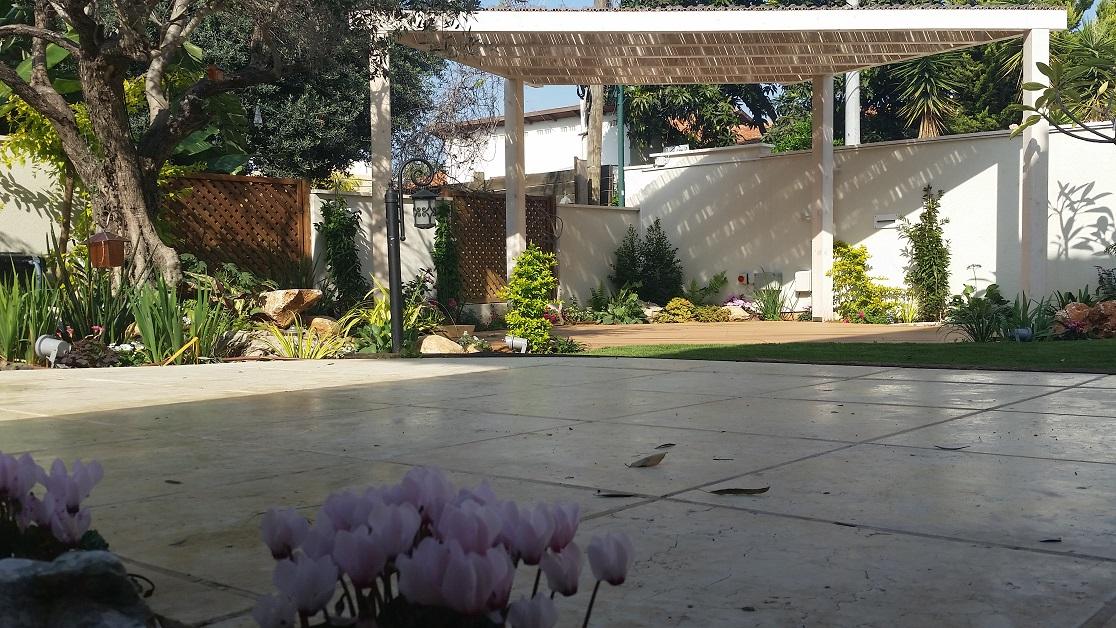 מבט מרחבת היציאה מהסלון אל פרגולה קטנה מעוצבת בצורה המתאימה לדק ולקווי הגינה