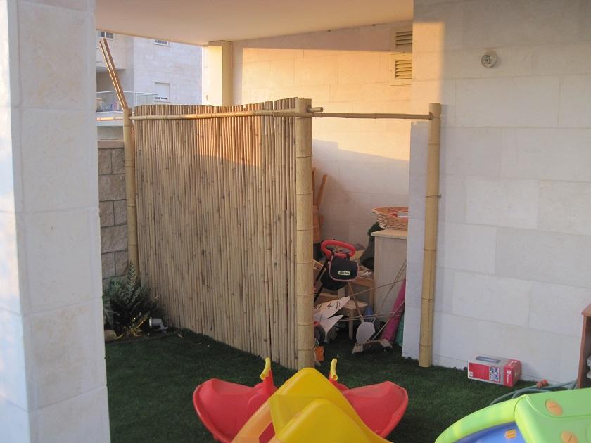 מחסן עשוי במבוק משולב בעיצוב הגינה כשהדשא סינתטי משתלב לתוכו ולצדדיו