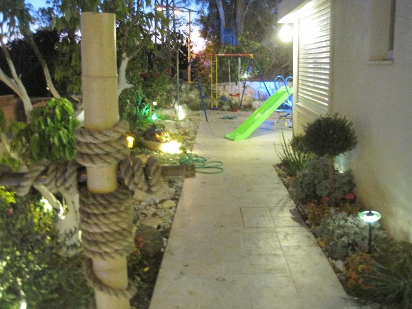 מבט לעומק לכיוון הגינה האחורית של הסלון ממול יש נדנדה ישנה שהיה חשוב להם לשלב