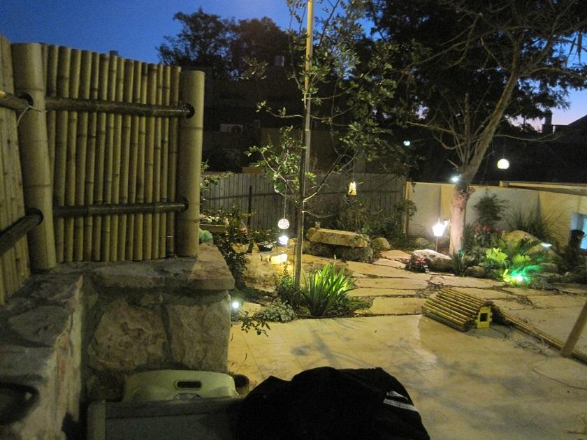 """אזור אחורי עם סלעי ספסל עיצוב צמחיה ובור חפור ויצוק בטון לבן בין סלעי הספסל וגדר במבוק ביצוע גם ע""""י ערבות"""