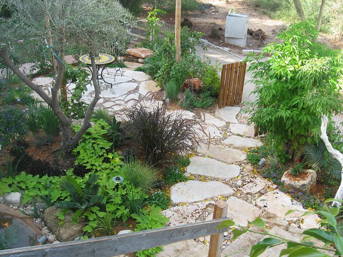 מבט ממדרגות העלייה לבית ניתן לשים לב שהשביל כניסה עשוי מאבני מדרך גדולות ומזמינות לדרוך ולהכנס