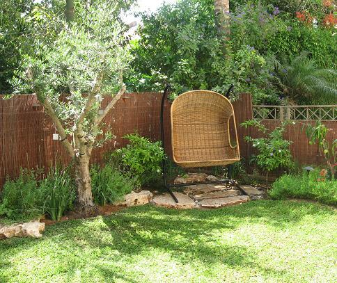 דשאמעוצב טופוגרפית בהתאמה לעיצוב הצמחיה שמסביב וספסל פינתי קטן על אבני מדרך שיצרנו בשבילו