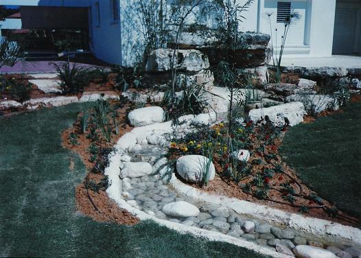 נחל זורם בגינה בשילוב עם חלוקי נחל דבוקים על היציקות