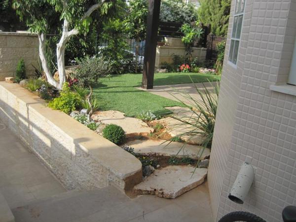 כניסה לאזור צדדי של הגינה נעשה חיתוך של החומה כדי לייצר הזמנה